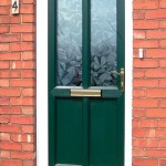 A green uPVC door with patterned glass